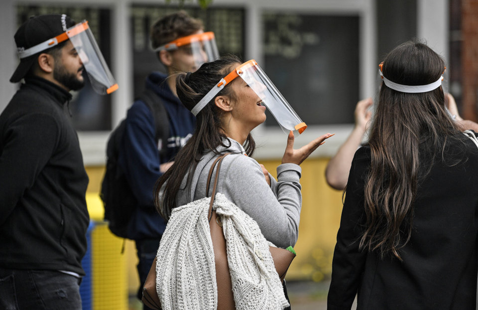Photo - Students try out a new face shield to fight the coronavirus pandemic at a school in Cologne, Germany, Monday, May 25, 2020. [AP Photo/Martin Meissner]
