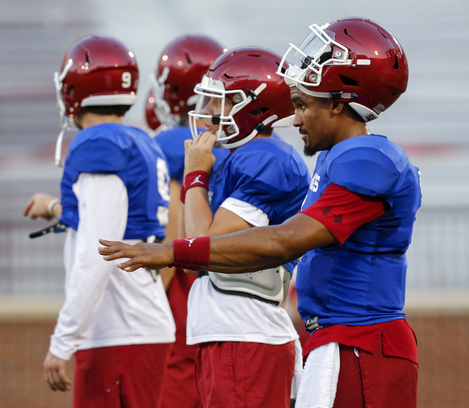 Photo - OU quarterback Jalen Hurts, right, stands near the other quarterbacks during football practice for the University of Oklahoma Sooners in Norman, Okla., Monday, Aug. 12, 2019. [Nate Billings/The Oklahoman]