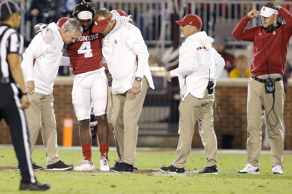 Photo - Oklahoma's Trey Sermon (4) is helped off the field after an injury during an NCAA football game between the University of Oklahoma Sooners (OU) and the Iowa State University Cyclones at Gaylord Family-Oklahoma Memorial Stadium in Norman, Okla., Saturday, Nov. 9, 2019. [Bryan Terry/The Oklahoman]