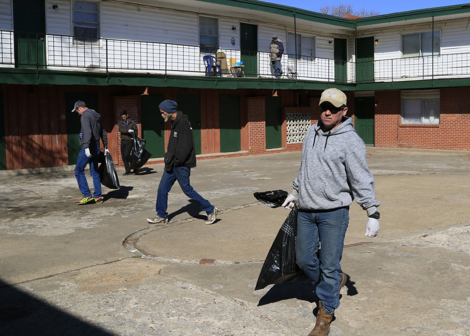 Photo -  Tony Wade and other volunteers work to clean up the grounds at Country Club Apartments in Oklahoma City as part of an Adopt-a-Block outreach event organized by the Oklahoma City Dream Center. [Photo by Paul Hellstern, The Oklahoman]
