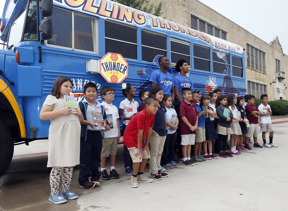 Photo - Oklahoma City guards Semaj Christon, left, and Cameron Payne pose for a photo with students during a stop by the Oklahoma City Thunder's Rolling Thunder Book Bus at Sequoyah Elementary, 2400 NW 36th St., in Oklahoma City, Thursday, Sept. 15, 2016. Photo by Nate Billings, The Oklahoman