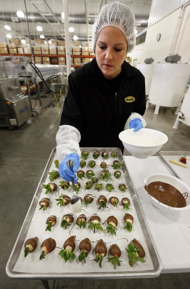 Photo - Melissa Walker drizzles white chocolate on chocolate-covered strawberries at Bedre Fine Chocolate on Friday, Feb. 6, 2015 in Davis, Okla. [The Oklahoman Archives]