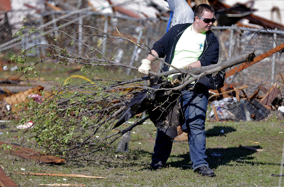 Photo - Jacob Bernier cleans up storm damage and debris in Moore, Okla. on Thursday, March 26, 2015. A tornado hit the area on Wednesday evening causing damage in the area.  Photo by Chris Landsberger, The Oklahoman