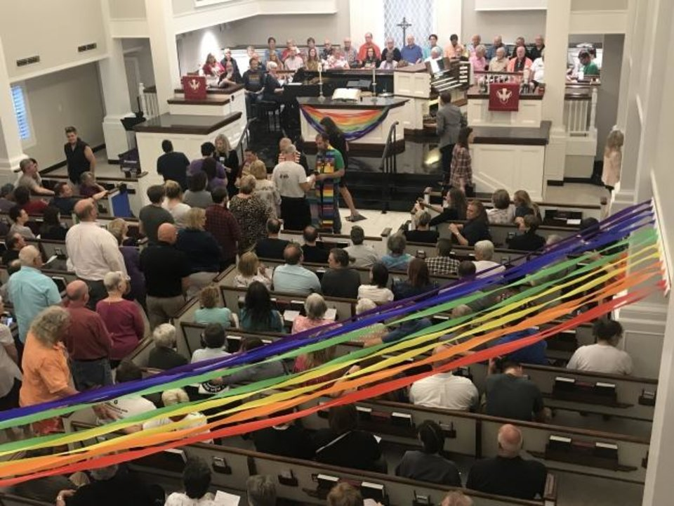 Photo -  People take Communion at the inaugural Ecumenical Pride Worship Service on Wednesday at Mayflower Congregational Church-United Church of Christ, 3901 NW 63. [Photo provided]
