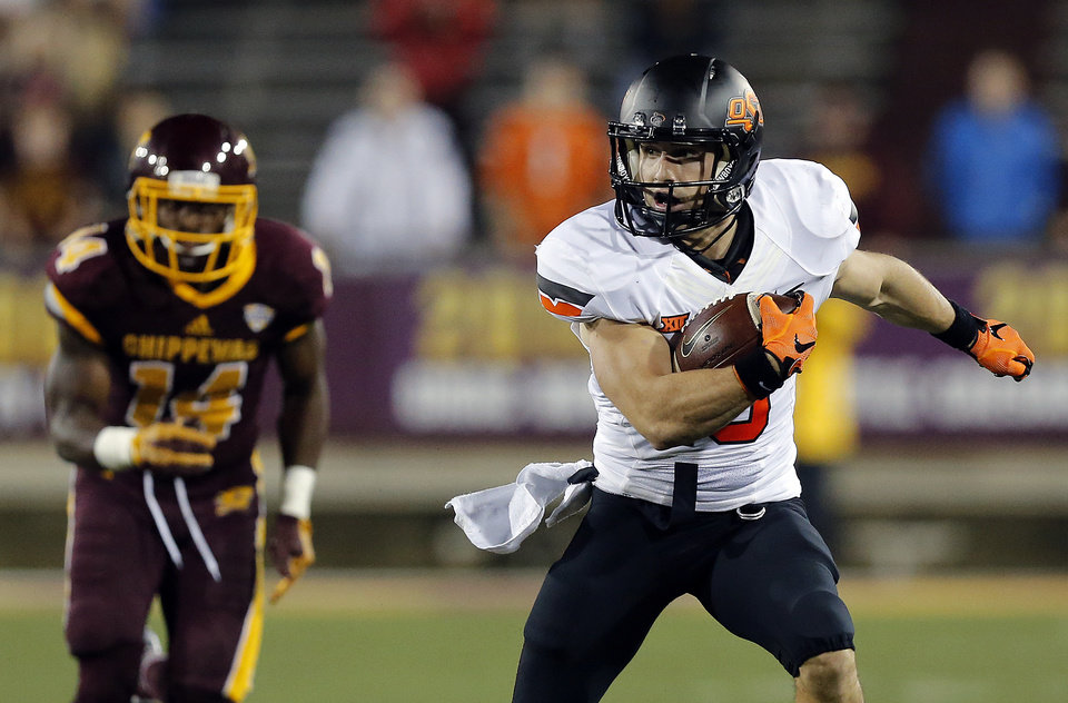 Photo - Oklahoma State's David Glidden (13) runs after a catch as Josh Cox (14) chases him during the college football game between the Central Michigan Chippewas and the Oklahoma State University Cowboys at the Kelly-Shorts Stadium in Mount Pleasant, Mich., Thursday, Sept. 3, 2015. Photo by Sarah Phipps, The Oklahoman