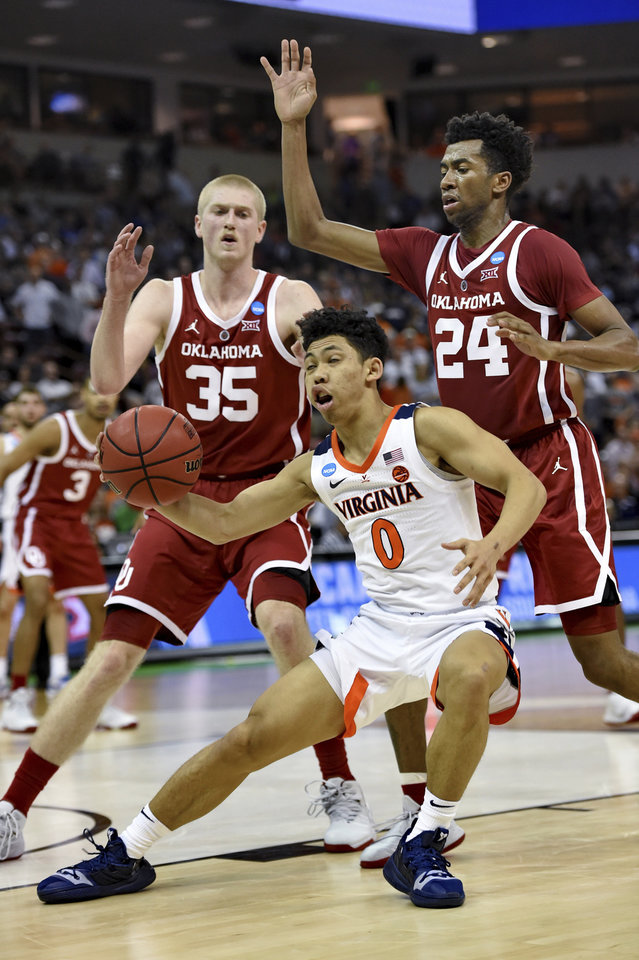 Photo - Virginia's Kihei Clark (0) is pressured under the basket by Oklahoma's Brady Manek (35) and Jamal Bieniemy (24) during the second half of a second-round men's college basketball game in the NCAA Tournament in Columbia, S.C., Sunday, March 24, 2019. (AP Photo/Richard Shiro)