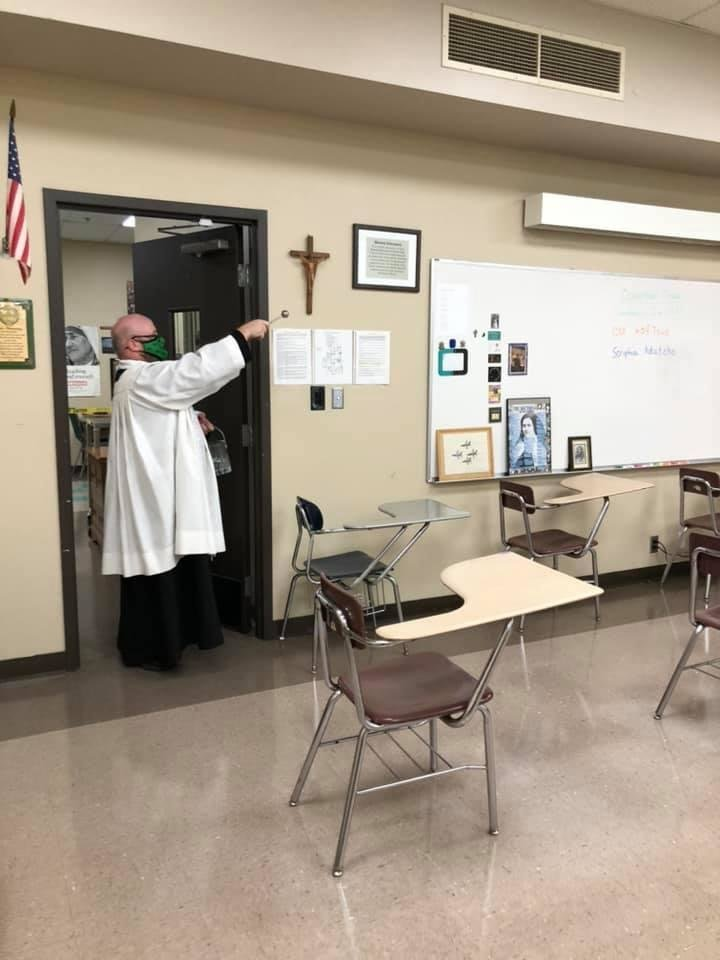 Photo -  Deacon Clyde Grover says a blessing over a classroom at Bishop McGuinness High School, where he was a faculty member. [provided]