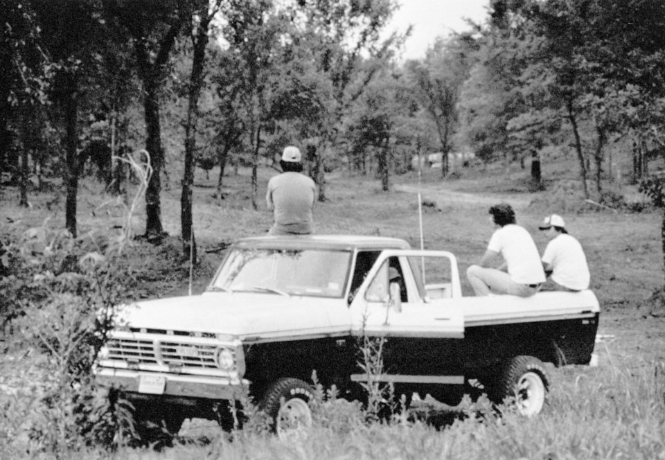 Photo -  These men, watching from their parked pickup, are part of several hundred people searching in rugged, wooded countryside of eastarn Oklahoma for the person who killed three young Girl Scouts on June 13, 1977. (AP File Photo)