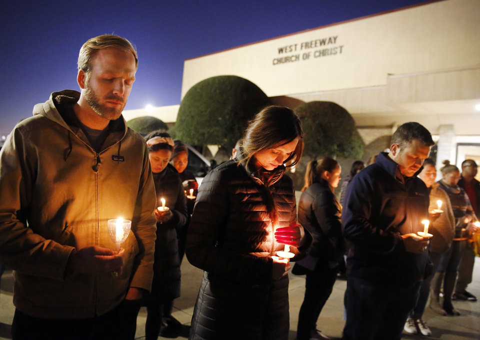 Photo -  Church and community members, including Matt Pacholczyk, left, and his wife, Faith Pacholczyk, stand outside West Freeway Church of Christ for a candlelight vigil, Monday in White Settlement, Texas. A gunman shot and killed two people before an armed security officer returned fire, killing him during a service at the church on Sunday. [Tom Fox/The Dallas Morning News via AP]