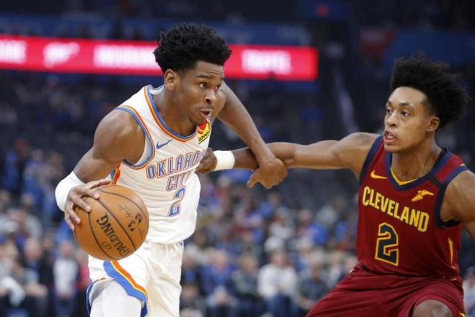 Photo -  Oklahoma City's Shai Gilgeous-Alexander, left, goes past Cleveland's Collin Sexton during Wednesday night's NBA game at Chesapeake Energy Arena. [Bryan Terry/The Oklahoman]