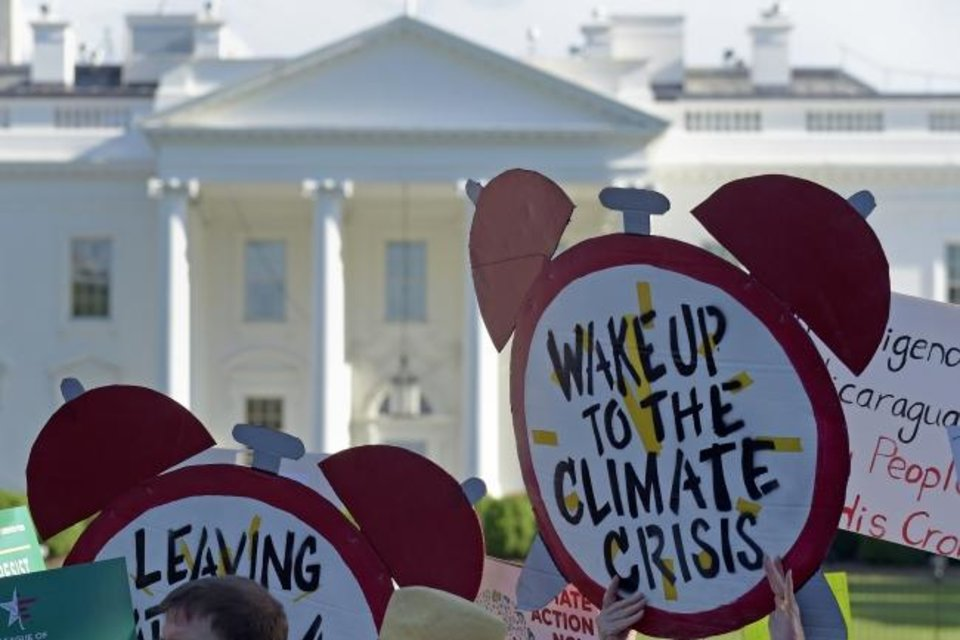 Photo -  In 2017, protesters gathered outside the White House in Washington to protest President Donald Trump's decision to withdraw the Unites States from the Paris climate change accord. Climate change has been a much-debated topic in recent years across the nation, but Oklahomans are still less likely to let this subject influence their vote in the upcoming presidential election. (AP Photo/Susan Walsh)