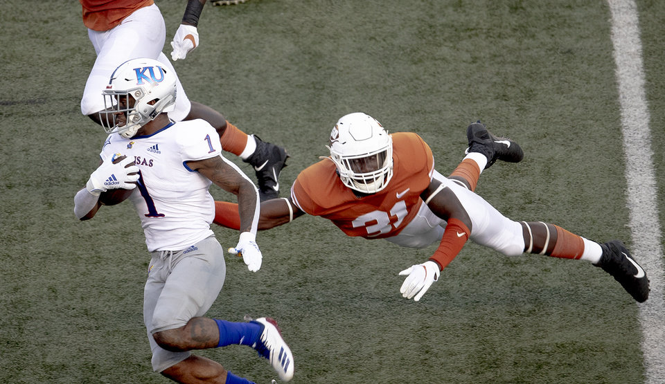 Photo - Texas defensive back DeMarvion Overshown (31) leaps  to tackle Kansas running back Pooka Williams Jr. (1)  during an NCAA college football game Saturday, Oct. 19, 2019, in Austin, Texas. (Nick Wagner/Austin American-Statesman via AP)