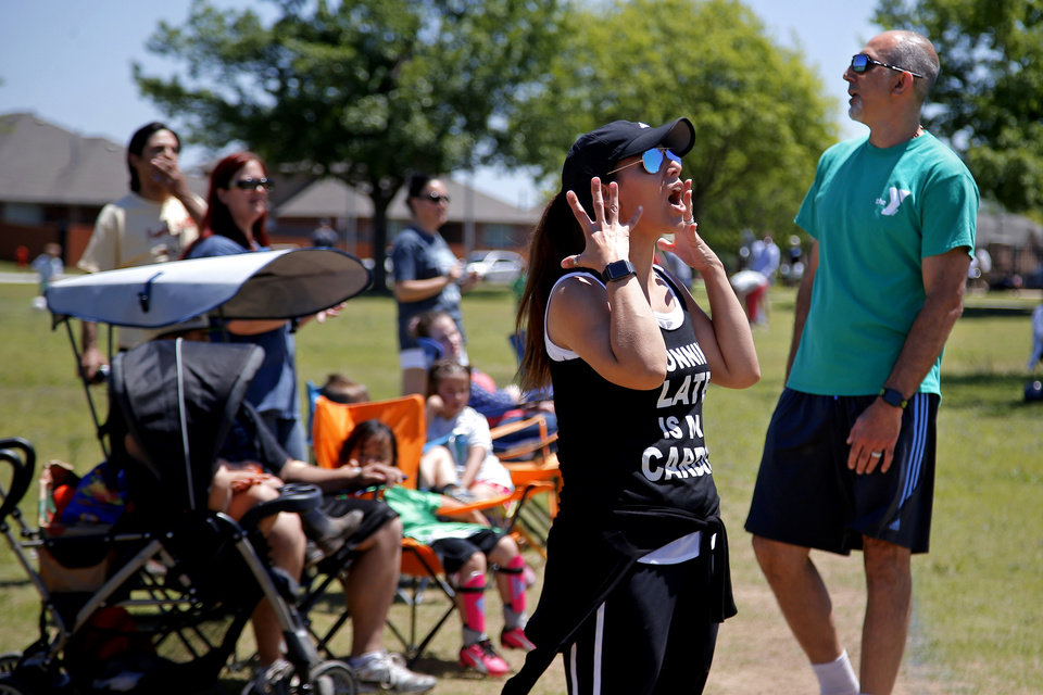 Photo -  Estabraq Al-Adhami and Nassil Abdullah react during their daughter's soccer game in Oklahoma City. [Photo by Bryan Terry, The Oklahoman]