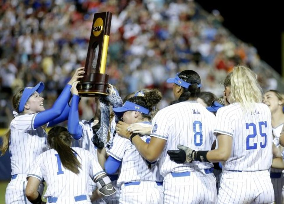 Photo -  UCLA hoists the NCAA softball championship trophy after beating Oklahoma 5-4 Tuesday in Game 2 of the Women's College World Series championship at USA Softball Hall of Fame Stadium. [Sarah Phipps/The Oklahoman]