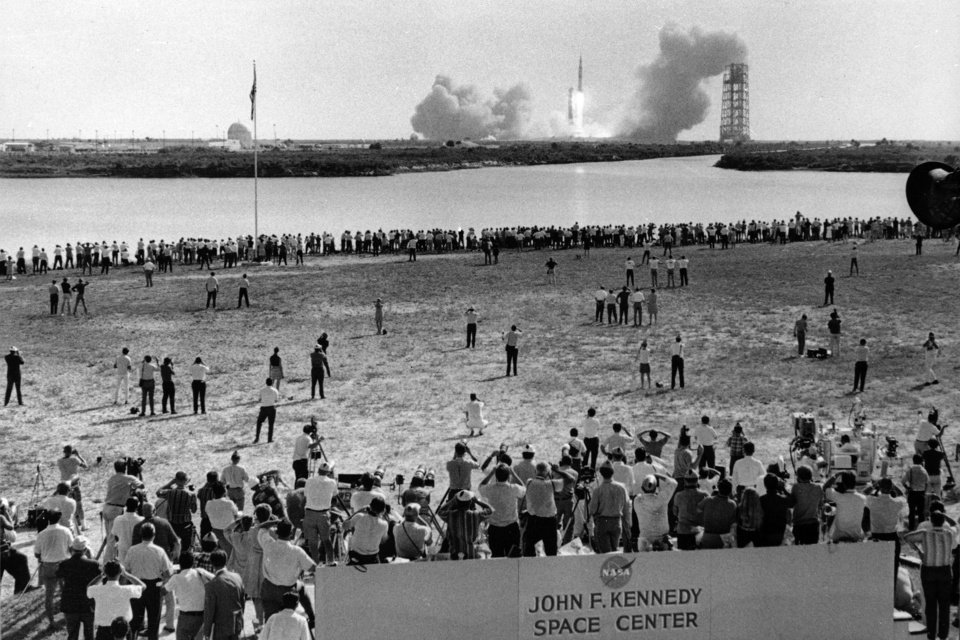 Photo -  FILE - In this July 16, 1969 file photo, reporters line the banks of a lagoon at the Cape Kennedy Press Site in Cape Canaveral as the Saturn V rocket with Apollo 11 astronauts aboard launches three-and-a-half miles away on their historic mission to the moon. (AP Photo)