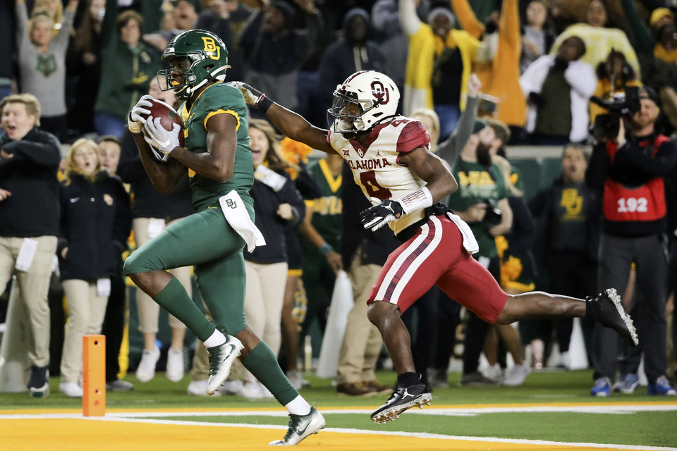Photo - Baylor wide receiver Denzel Mims, left, makes a 30-yard touchdown catch as Oklahoma cornerback Jaden Davis, right, defends during the first half of an NCAA college football game in Waco, Texas, Saturday, Nov. 16, 2019. (AP Photo/Ray Carlin)