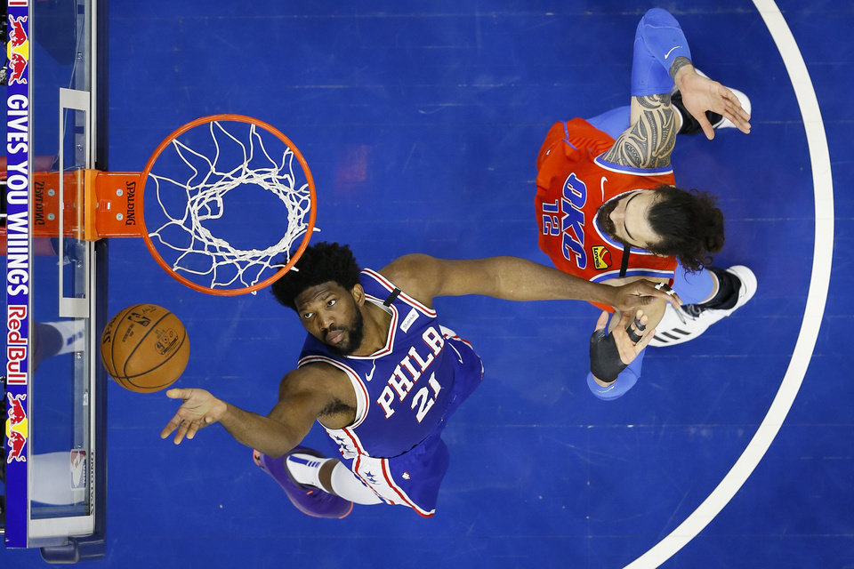 Photo - Philadelphia 76ers' Joel Embiid, left, goes up to shoot against Oklahoma City Thunder's Steven Adams during the first half of an NBA basketball game, Monday, Jan. 6, 2020, in Philadelphia. (AP Photo/Matt Slocum)
