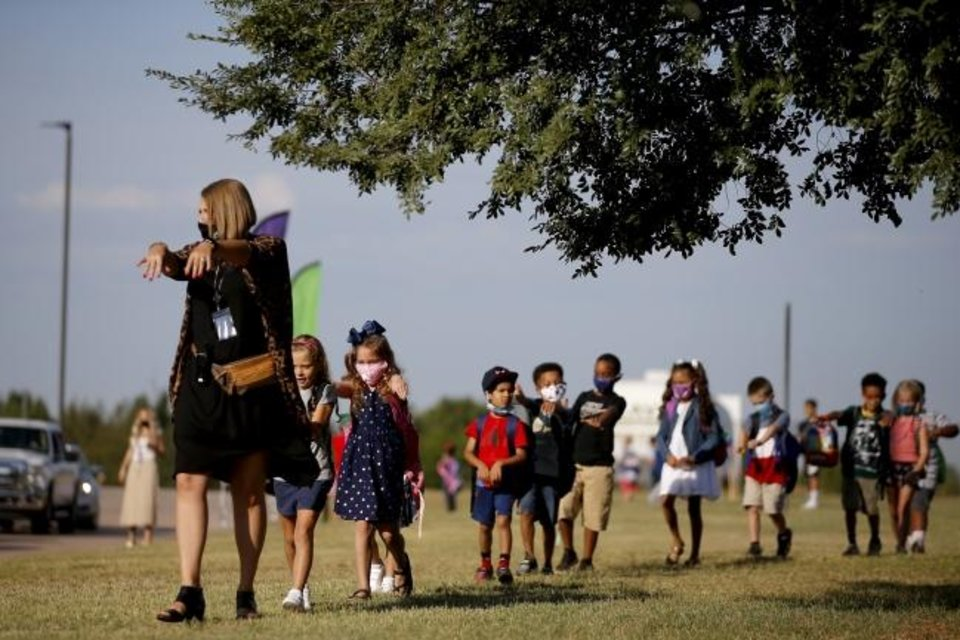 Photo -  Assistant principal Amanda Neely holds her arms out to demonstrate how to stay spaced apart as she lines up students for their first day of school Thursday at Edmond Public Schools' Charles Haskell Elementary. [Bryan Terry/The Oklahoman]