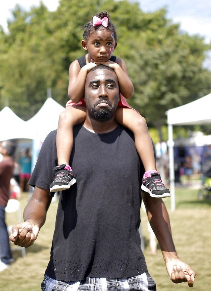 Photo - Curtis Elam dances with Zamya Elam, 4, during the Wiggle Out Loud family music festival presented by The Children's Hospital at the Myriad Botanical Gardens Great Lawn in Oklahoma City, Sunday, Sept. 16, 2018. [Sarah Phipps/The Oklahoman Archives]
