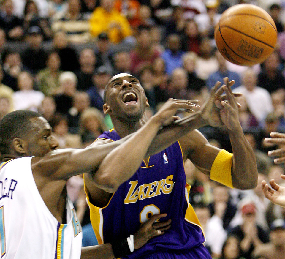 Photo - New Orleans/Oklahoma City Hornets guard Kirk Snyder, left, fouls Los Angeles Lakers guard Kobe Bryant (8) in the first half of Saturday night's NBA basketball game Feb. 4, 2006 in Oklahoma City. (AP Photo/Ty Russell)