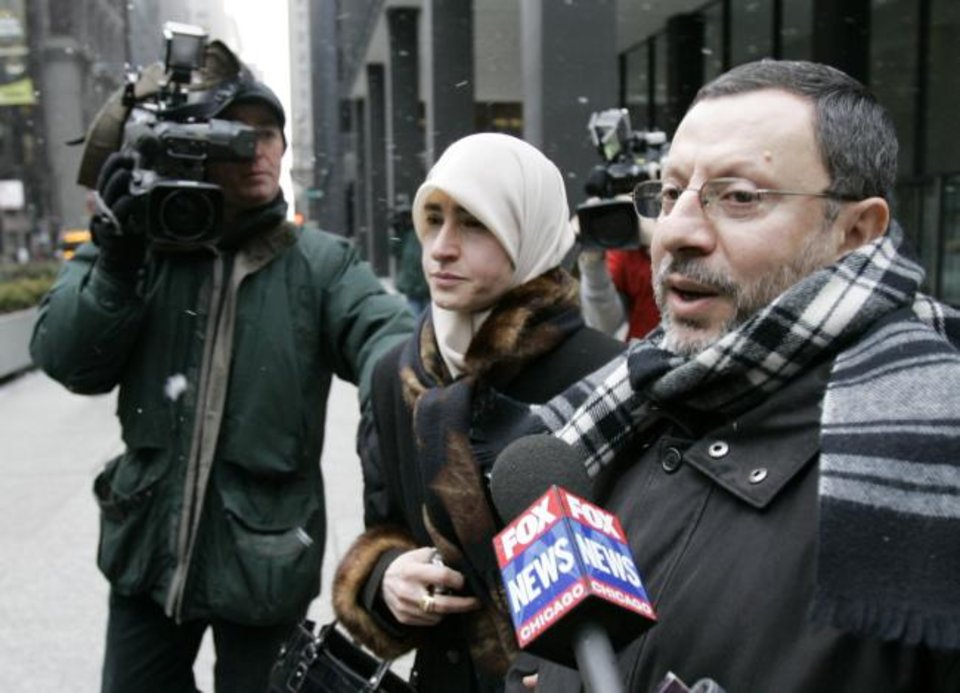 Photo - FILE - In this Feb. 1, 2007 file photo, Abdelhaleem Ashqar is surrounded by cameramen as he leaves federal court with his wife, in Chicago. Ashquar who says he fears torture at the hands of Israeli authorities,  is back in the U.S. after a judge's order forced immigration authorities to reverse his deportation and bring him back from Israel before he ever got off the plane.  According to court papers and interviews, U.S. authorities arrested and deported Ashqar Tuesday, June 4, 2019  after misleading him about his need to report to an immigration office to process paperwork.  (AP Photo/Charles Rex Arbogast)