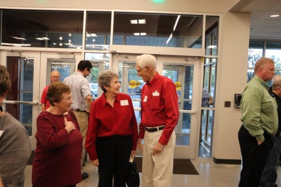 Photo -  Max Barnett, former Baptist Student Ministries director at the University of Oklahoma, right, welcomes visitors to the dedication of the new Baptist Collegiate Ministry building on the OU campus. [Baptist Messenger]