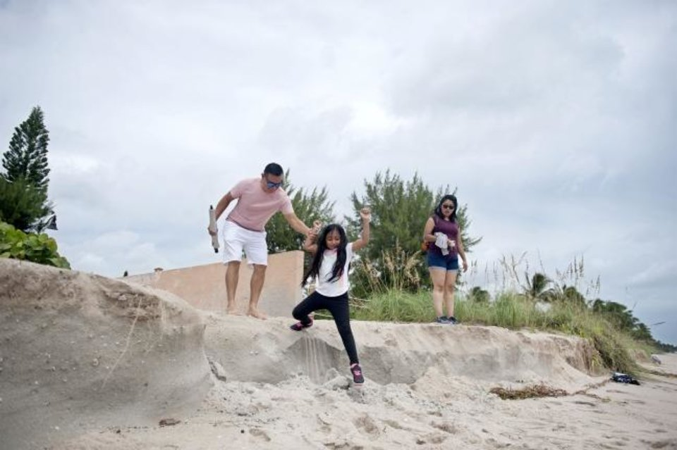 Photo -  Jose and Jayla Lopez, 7, and Jeanette Perez, all from West Palm Beach, Fla., climb down a drop-off caused by erosion from Hurricane Dorian at the beach Wednesday. [MEGHAN MCCARTHY/GateHouse Media]