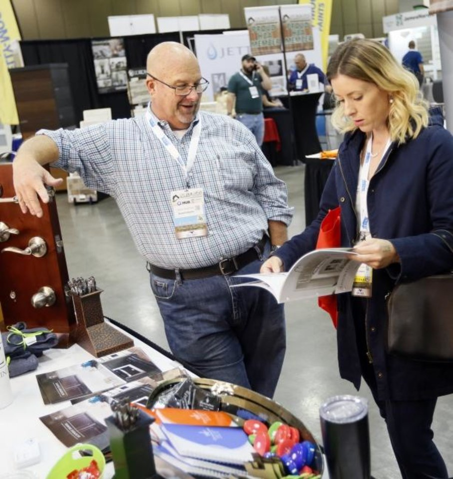 Photo -  From left, Steve Andrews from Illuminations talks to Jennifer Giesecke of Home Creations during the OK Building Summit & Expo at the Cox Convention Center.  [NATE BILLINGS/THE OKLAHOMAN]