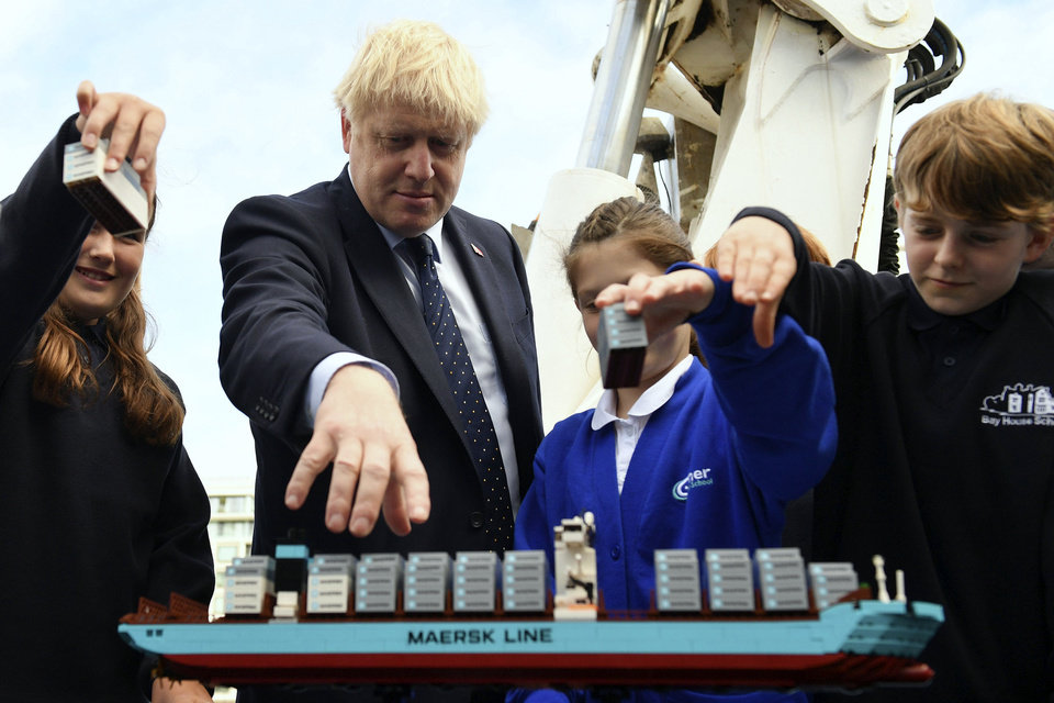 Photo -  Britain's Prime Minister Boris Johnson takes part in an activity with school children as he visits the NLV Pharos, a lighthouse tender moored on the river Thames, to mark London International Shipping Week in London, Thursday, Sept. 12, 2019. The British government insisted Thursday that its forecast of food and medicine shortages, gridlock at ports and riots in the streets after a no-deal Brexit is an avoidable worst-case scenario, as Prime Minister Boris Johnson denied misleading Queen Elizabeth II about his reasons for suspending Parliament just weeks before the country is due to leave the European Union. (Daniel Leal-Olivas/Pool photo via AP)