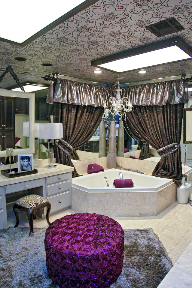 Photo - The master bathroom suite at the 2012 Symphony Show House was decorated by Susan Tiffin and Rhonda Nixon who were inspired by the Hollywood glamour of Liz Taylor. The designers made the bathtub a focal point by framing it with dramatic drapes and wallpapered the ceiling with a graphic floral wallpaper. Photo by Chris Landsberger, The Oklahoman.  CHRIS LANDSBERGER