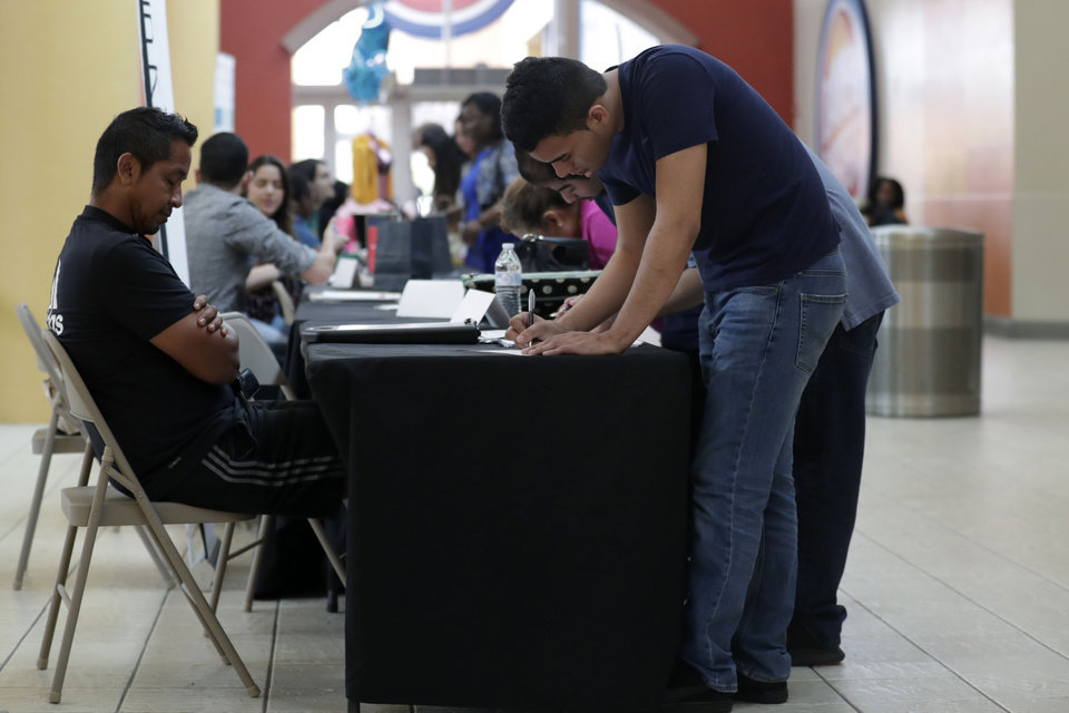Photo -  Billy Ramos, right, fills out a job application with Adidas during a job fair at Dolphin Mall in Miami. [AP PHOTO]