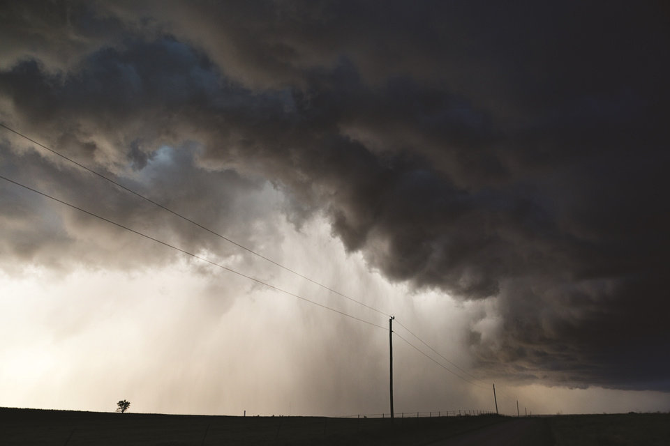Photo -  Ominous clouds move toward power lines in Oklahoma in June 2013. [Photo by Camille Seaman]