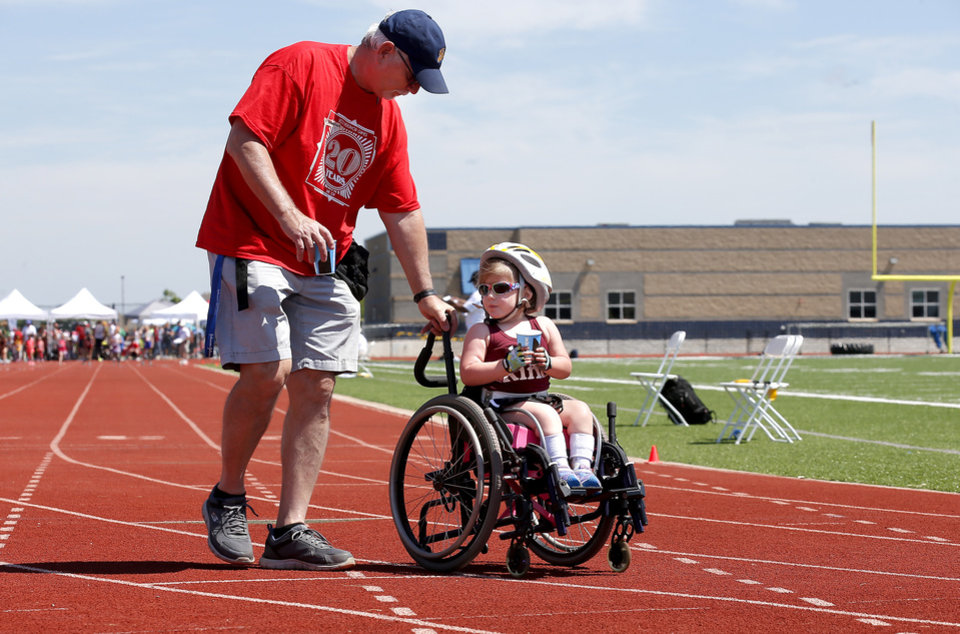 Photo -  Ed Sunderland helps Poppy Cox after the 60-meter dash the during the Endeavor Games at Edmond North High School on Saturday. [Sarah Phipps/The Oklahoman]