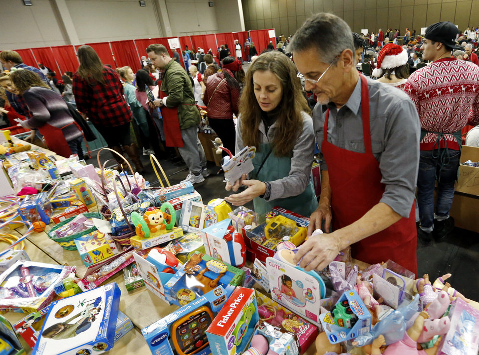 Photo - David Stejskal and his daughter Brandi retrieve toys to distribute during the annual Red Andrews Christmas Dinner in the Cox Convention Center on Monday, Dec. 25, 2017 in Oklahoma City, Okla.  Photo by Steve Sisney, The Oklahoman