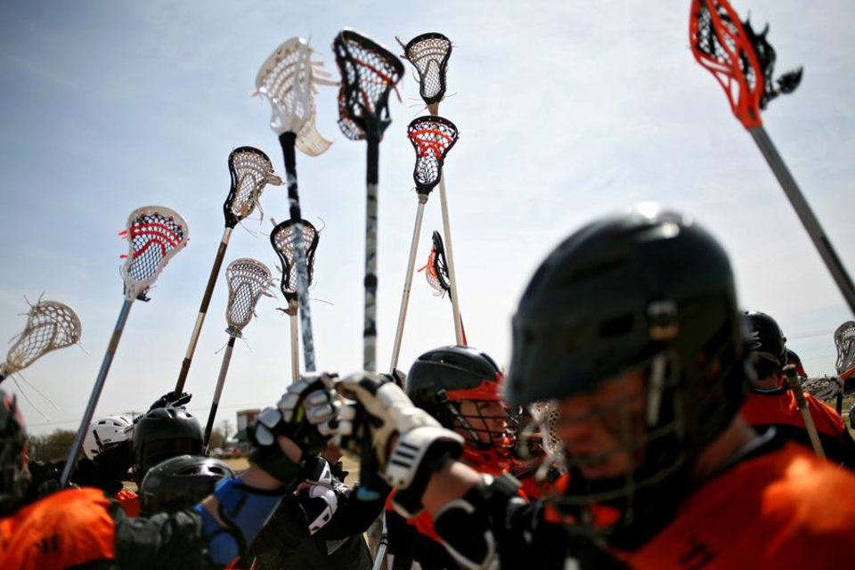 Photo -  UNIVERSITIY OF OKLAHOMA / OKLAHOMA STATE UNIVERSITY / OU / OSU: Oklahoma State's lacrosse team hold up their sticks after getting instructions during a timeout in the Bedlam lacrosse game outside Cheyenne Middle School in Edmond, Okla., on Sunday, March. 6, 2011. Photo by John Clanton, The Oklahoman ORG XMIT: KOD