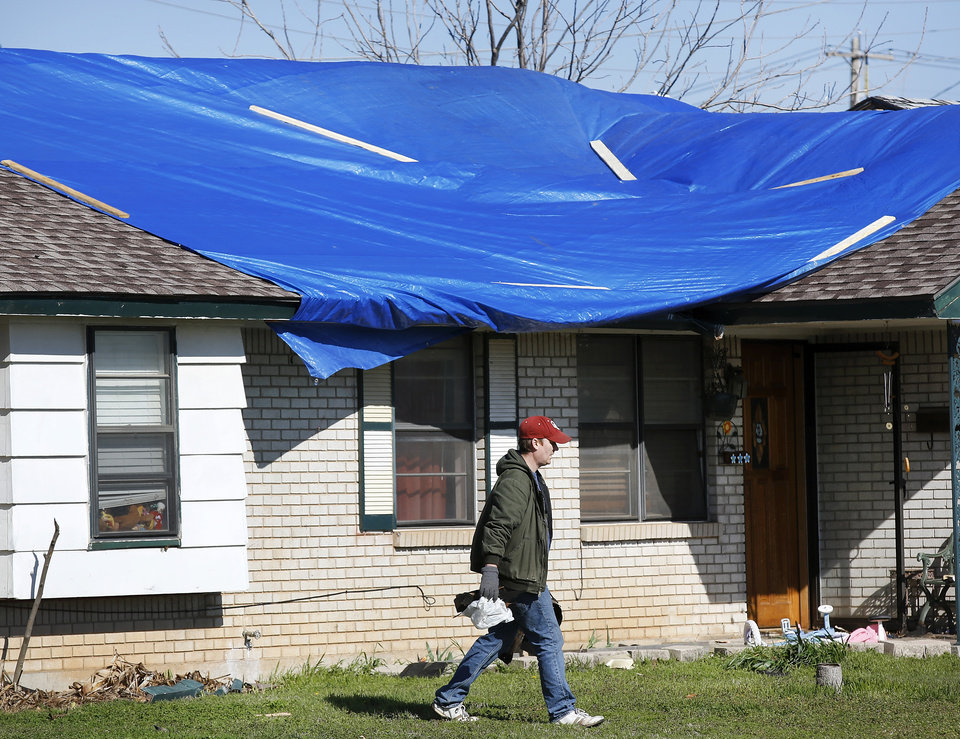 Photo - A tarp covers the roof of this home at 409 N. Norman Ave in Moore. Neighborhood  between NW 5 and Main Street, and between Telephone Rd. and Santa Fe in Moore.  Thursday morning, March 26, 2015, the day after a tornado damaged homes and a school Wednesday evening. Photo by Jim Beckel, The Oklahoman