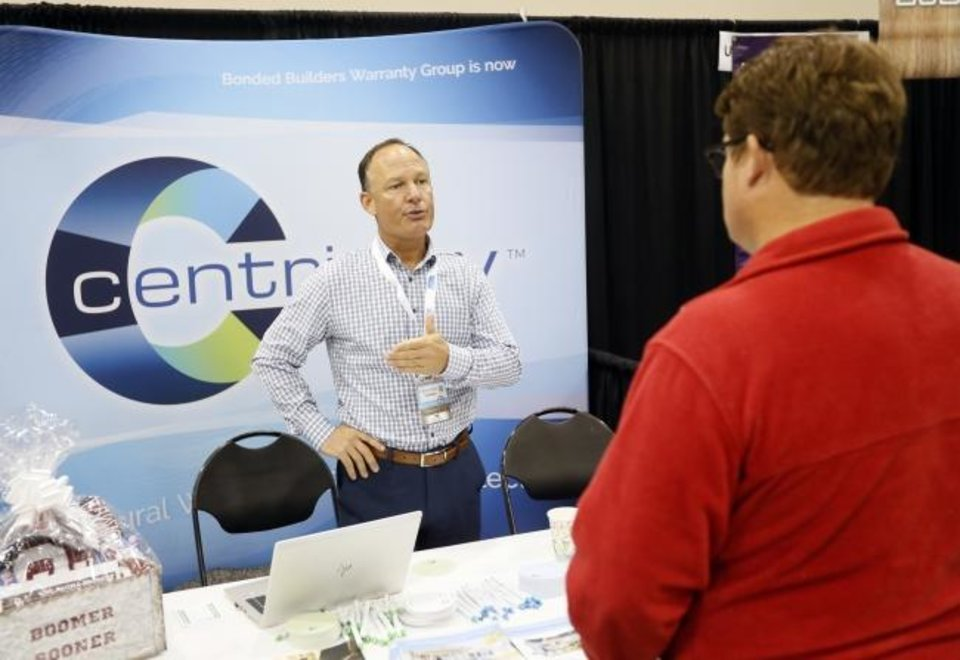 Photo -  Steve Hooker from Centricity, left, talks with Clark Edwards of Edwards Custom Homes during the OK Building Summit & Expo at the Cox Convention Center. [NATE BILLINGS/THE OKLAHOMAN]