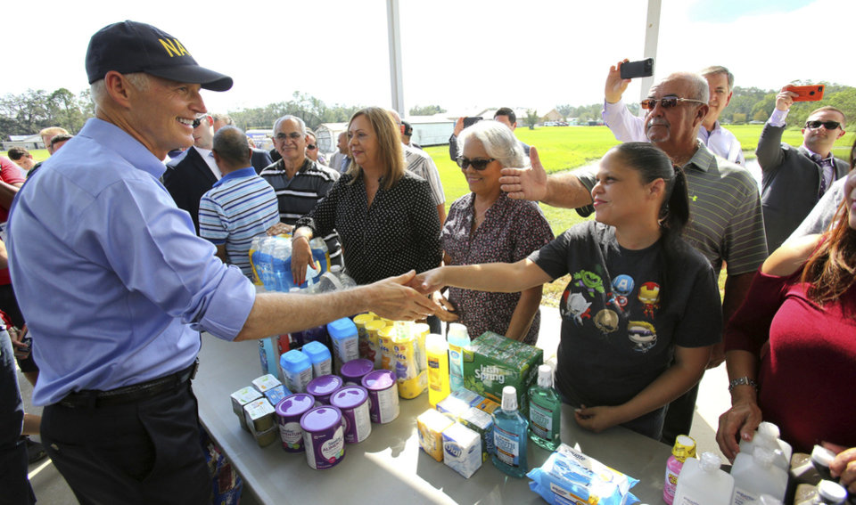 Photo - Florida Governor Rick Scott thanks Osceola County volunteers who are assisting with the relief effort for Puerto Rico in the wake of Hurricane Maria, during a visit to the Osceola County Services warehouse, in Kissimmee, Fla., Wednesday, Sept. 27, 2017. (Joe Burbank/Orlando Sentinel via AP)