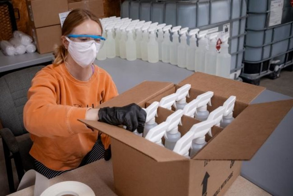 Photo -  Emma Haley boxes up bottles of Okie Clean hand sanitizer and all purpose cleaner at the Okie Clean warehouse. [Chris Landsberger/The Oklahoman]