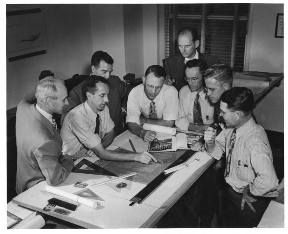 Photo -  Truett Coston, fourth from the right looking over the shoulders of his colleagues, joined Wally Frankfurt, third from the left, to found what is now FSB in 1945. They soon  were joined by Harold Short, far left, as the firm  expanded with a balance of both architects and engineers. The firm's first offices, shown here, were in APCO Tower, the skyscraper now known as City Place, 204 N Robinson Ave. downtown. [PHOTO PROVIDED BY FSB]