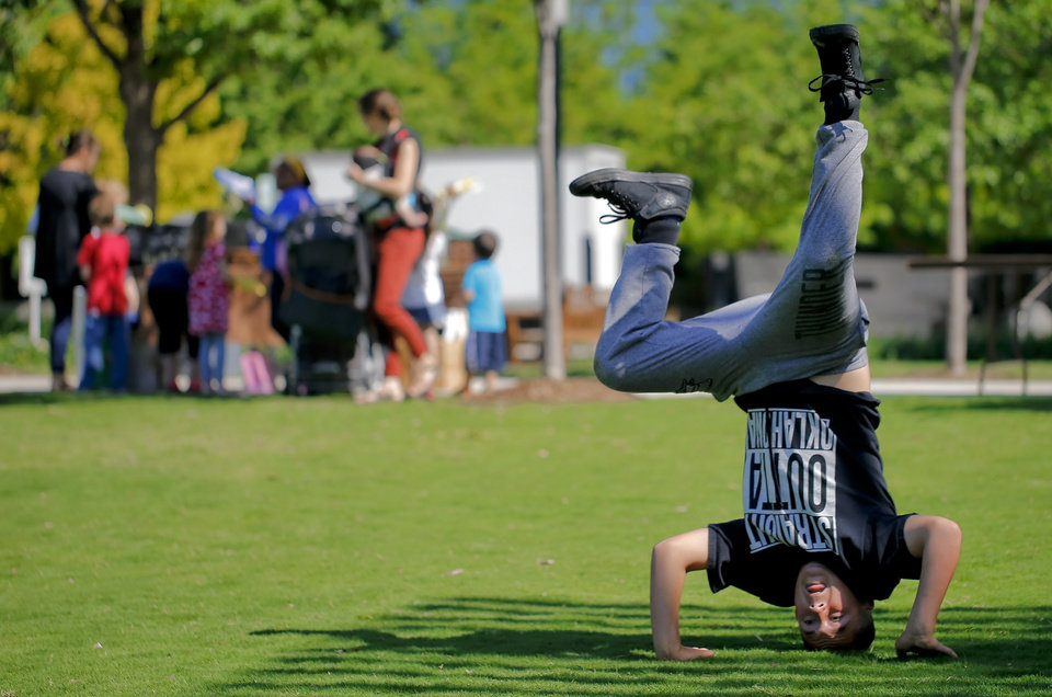 Photo - Johnathan Sosa, 12, does a headstand while playing on the Great Lawn during the Myriad Botanical Gardens Earth Day celebration in Oklahoma City, Okla. on Friday, April 22, 2016..  Photo by Chris Landsberger, The Oklahoman