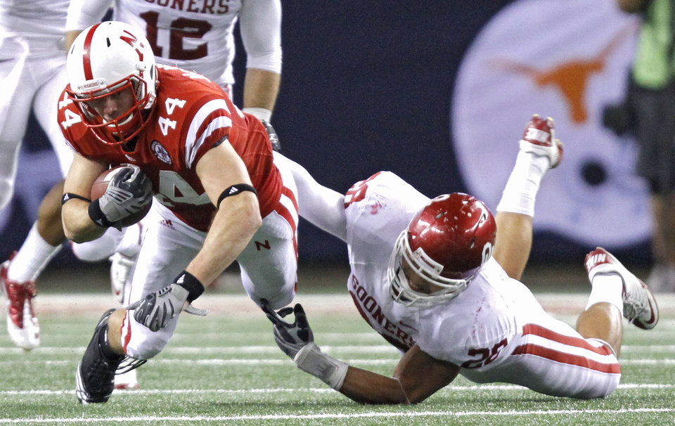 Photo - Oklahoma's Travis Lewis (28) brings down Nebraska's Mike McNeill (44) during the Big 12 football championship game between the University of Oklahoma Sooners (OU) and the University of Nebraska Cornhuskers (NU) at Cowboys Stadium on Saturday, Dec. 4, 2010, in Arlington, Texas.  Photo by Chris Landsberger, The Oklahoman
