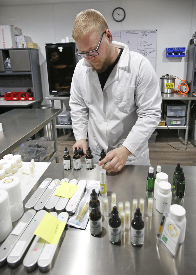 Photo -  Lab technician Tanner Hand labels Cannabidiol products at Can-Tek Labs in Oklahoma City, Wednesday, 25 2017. The company offers a variety of products infused with organically grown, non-GMO hemp extract that is naturally rich in Cannabidiol. [Photo By Steve Gooch, The Oklahoman]