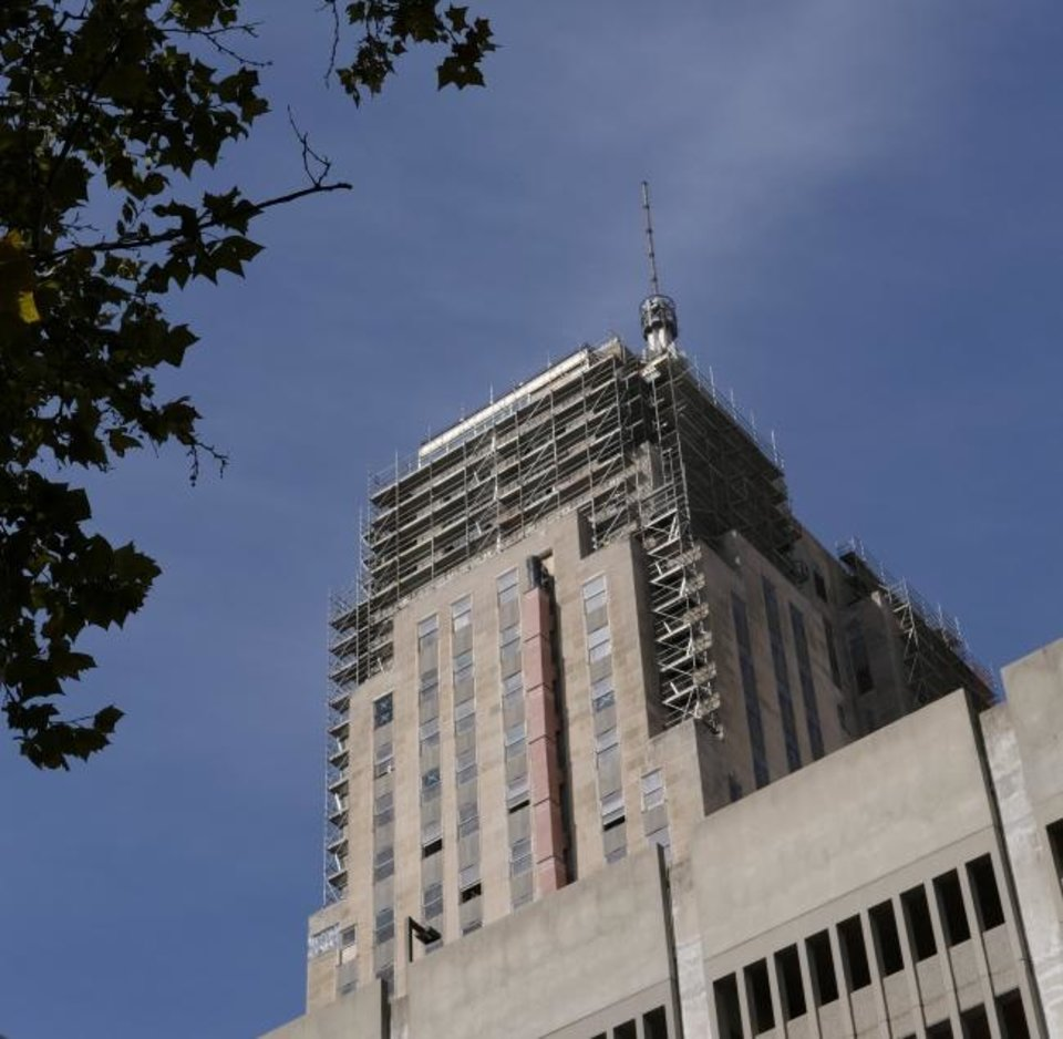 Photo -  Scaffolding surrounds the top of the First National as crews secure limestone panels and repair glass and frames on the floors that were once home to the Beacon Club. [DOUG HOKE/THE OKLAHOMAN]