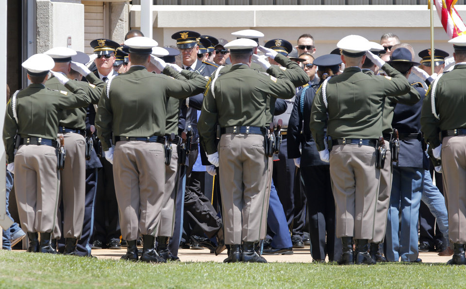 Photo - The honor guard salutes family members as they arrive for Logan County Deputy David Wade's funeral service in Guthrie, Monday April 24, 2017. Photo By Steve Gooch, The Oklahoman