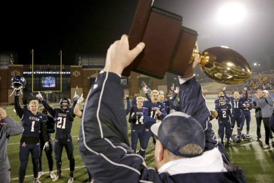 Photo -  Tulsa Metro Christian celebrates with the Class 2A championship trophy Saturday. [Bryan Terry/The Oklahoman]