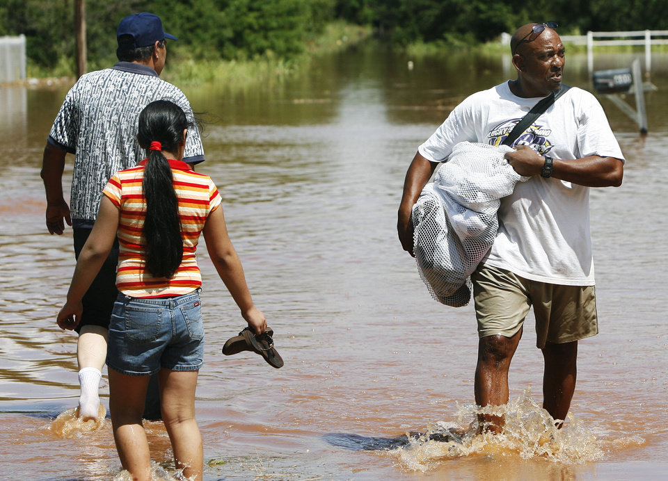 Photo - People attempting to retrieve items from their homes as flood waters continue to rise on Sunday, August 19, 2007, in Kingfisher, Okla. By James Plumlee, The Oklahoman.