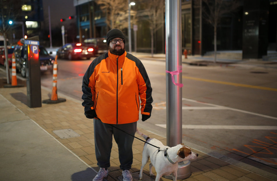 Photo - Cody Lusnia,with his dog Rip, next to a light pole in downtown Oklahoma City. Lusnia mapped 419 nonworking lights downtown and in Midtown, prompting action by the city to restore them to service. [Photo by Sarah Phipps, The Oklahoman]
