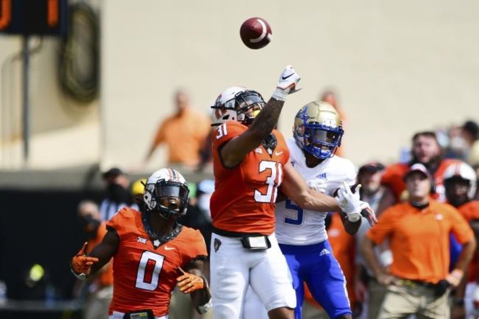 Photo -  Oklahoma State cornerback Christian Holmes (0) watches as teammate Kolby Harvell-Peel (31) knocks the ball away from Tulsa receiver Sam Crawford Jr (9). in the second half Saturday in Stillwater. [AP Photo/Brody Schmidt]