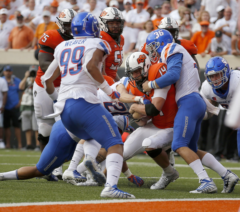 Photo - Oklahoma State's Taylor Cornelius (14) rushes for a touchdown as Boise State's Blake Whitlock (36) defends in the fourth quarter during a college football game between the Oklahoma State Cowboys (OSU) and the Boise State Broncos at Boone Pickens Stadium in Stillwater, Okla., Saturday, Sept. 15, 2018. OSU won 44-21. Photo by Sarah Phipps, The Oklahoman